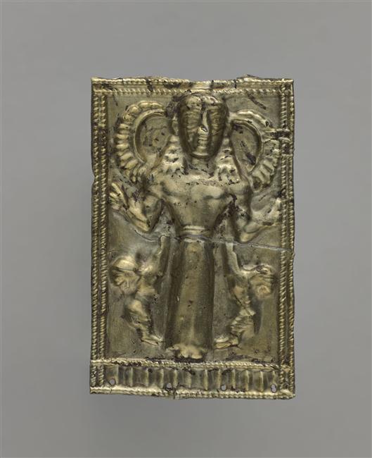 Plaquette rectangulaire en alliage d'argent et d'or représentant une femme ailée debout, paumes levées, flanquée de deux lions dressés.